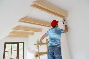 handyman paints interior walls of home
